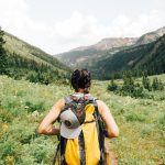 girl hiking in mountains with backpack
